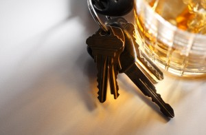 Car keys next to a glass of alcohol